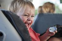 Toddler boy laughing in car 11001064481| 写真素材・ストックフォト・画像・イラスト素材|アマナイメージズ