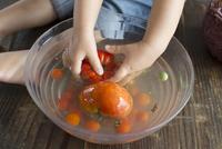Child washing tomatoes