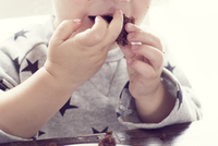 Child eating cake with hands
