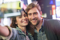 Young couple taking selfie in illuminated city street