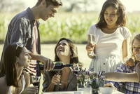 Friends chatting while enjoying drink together outdoors 11001064589| 写真素材・ストックフォト・画像・イラスト素材|アマナイメージズ