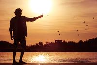 Man using cell phone to photograph sunset 11001064605| 写真素材・ストックフォト・画像・イラスト素材|アマナイメージズ
