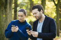 Couple checking smartphones while walking in woods