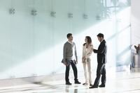 Business associates chatting in office corridor 11001064691| 写真素材・ストックフォト・画像・イラスト素材|アマナイメージズ