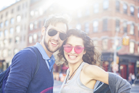 Young couple smiling together in urban setting, portrait