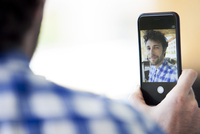 Man using smarthphone to take a selfie 11001064777| 写真素材・ストックフォト・画像・イラスト素材|アマナイメージズ