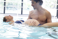 Pregnant woman exercising with help of fitness trainer in swimming pool