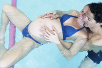 Pregnant woman exercising in swimming pool with help of partner and flotation devices
