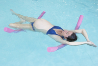 Pregnant woman exercising in swimming pool with flotation devices 11001064811| 写真素材・ストックフォト・画像・イラスト素材|アマナイメージズ
