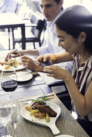 Woman using smarphone to photograph her meal in restaurant 11001064813| 写真素材・ストックフォト・画像・イラスト素材|アマナイメージズ