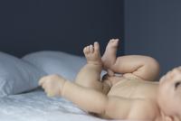 Baby lying on bed 11001064877| 写真素材・ストックフォト・画像・イラスト素材|アマナイメージズ