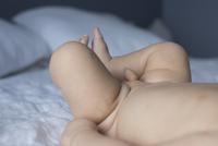 Baby boy lying on bed 11001064878| 写真素材・ストックフォト・画像・イラスト素材|アマナイメージズ