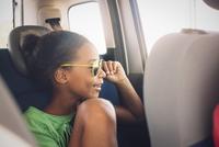 Girl looking out car window 11001064936| 写真素材・ストックフォト・画像・イラスト素材|アマナイメージズ