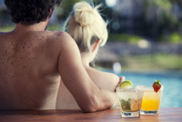 Couple relaxing at poolside with cocktails 11001064948| 写真素材・ストックフォト・画像・イラスト素材|アマナイメージズ