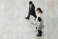 Business associates walking together in office lobby 11001064976| 写真素材・ストックフォト・画像・イラスト素材|アマナイメージズ