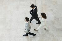 Business people walking through office lobby 11001064977| 写真素材・ストックフォト・画像・イラスト素材|アマナイメージズ