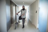 Man walking through corridor with bicycle