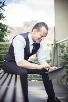 Businessman using digital tablet outdoors 11001065076| 写真素材・ストックフォト・画像・イラスト素材|アマナイメージズ
