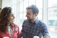 Cheerful couple talking together in coffee shop