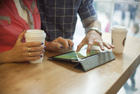 Couple using digital tablet in coffee shop, cropped