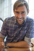 Man sitting in coffee shop with credit card in hand, smiling cheerfully
