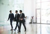 Business associates chatting while walking together 11001065096| 写真素材・ストックフォト・画像・イラスト素材|アマナイメージズ