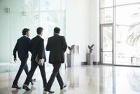 Business associates chatting while walking together 11001065097| 写真素材・ストックフォト・画像・イラスト素材|アマナイメージズ