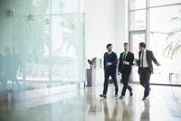 Business associates chatting while walking together 11001065099| 写真素材・ストックフォト・画像・イラスト素材|アマナイメージズ