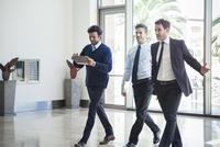 Business associates chatting while walking together 11001065104| 写真素材・ストックフォト・画像・イラスト素材|アマナイメージズ