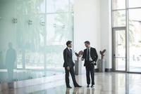 Business associates talking in office lobby 11001065113| 写真素材・ストックフォト・画像・イラスト素材|アマナイメージズ