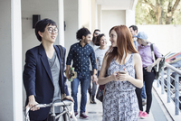 Coworkers chatting as they leave the office 11001065142| 写真素材・ストックフォト・画像・イラスト素材|アマナイメージズ
