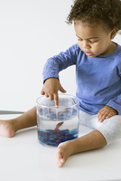 Toddler girl playing with pet goldfish 11001065162| 写真素材・ストックフォト・画像・イラスト素材|アマナイメージズ