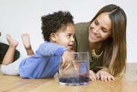 Mother and toddler daughter playing with pet goldfish
