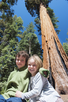 Young siblings sitting together under a giant sequoia tree