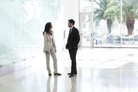 Business associates talking in office corridor 11001065286| 写真素材・ストックフォト・画像・イラスト素材|アマナイメージズ