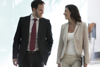 Colleagues chatting while walking together in office 11001065296| 写真素材・ストックフォト・画像・イラスト素材|アマナイメージズ