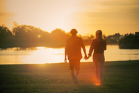 Couple walking hand in hand at water's edge 11001065312| 写真素材・ストックフォト・画像・イラスト素材|アマナイメージズ