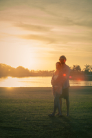 Couple standing together in park, bathed in sunlight 11001065314| 写真素材・ストックフォト・画像・イラスト素材|アマナイメージズ