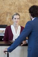 Hotel receptionist assisting guest 11001065343| 写真素材・ストックフォト・画像・イラスト素材|アマナイメージズ