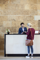 Woman text messaging during transaction with receptionist 11001065350| 写真素材・ストックフォト・画像・イラスト素材|アマナイメージズ