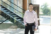 Young businessman standing in hotel lobby 11001065362| 写真素材・ストックフォト・画像・イラスト素材|アマナイメージズ