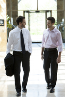 Business colleagues chatting while walking together 11001065381| 写真素材・ストックフォト・画像・イラスト素材|アマナイメージズ