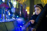 Little girl window shopping at night