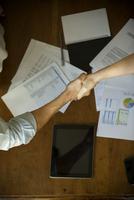 Business associates shaking hands during meeting 11001065414| 写真素材・ストックフォト・画像・イラスト素材|アマナイメージズ