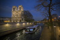 A pleasure boat moves past Notre Dame Cathedral on the Seine River at twilight, Paris, France