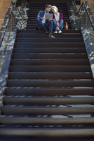 Couple sitting at top of stairs, using digital tablet together 11001065549| 写真素材・ストックフォト・画像・イラスト素材|アマナイメージズ