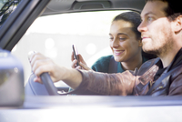 Couple listen to music streaming on smartphone during road trip