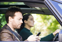 Man reading text messages while riding in car