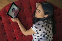 Woman blowing kiss at boyfriend while video conferencing on digital tablet 11001065617| 写真素材・ストックフォト・画像・イラスト素材|アマナイメージズ