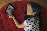 Woman video conferencing with boyfriend on digital tablet 11001065618| 写真素材・ストックフォト・画像・イラスト素材|アマナイメージズ